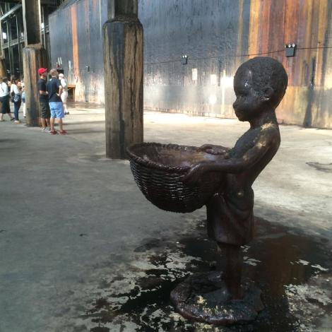 Molasses sculptures of working children inside the factory